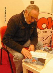 Marcello Toninelli firma dediche per i lettori, durante il suo incontro col pubblico a Wow Spazio Fumetto, lo scorso novembre