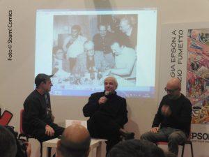 Da sinistra: Luca Boschi, Marco Rota e Davide Catenacci; sopra di loro, la foto dello storico incontro tra Carl Barks (seduto al centro, con la giacca a quadri) che si scambia disegni con Romano Scarpa (a destra)